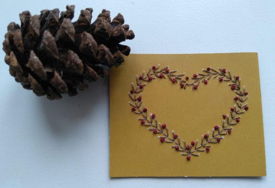 Hjerte broderet på genbrugs papir før syet på kort