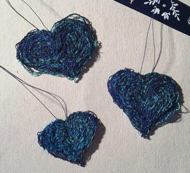 Tre blå hjerter syet på opløseligt stof