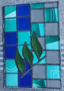 Papir patchwork i grå og blå farver og med et par blade