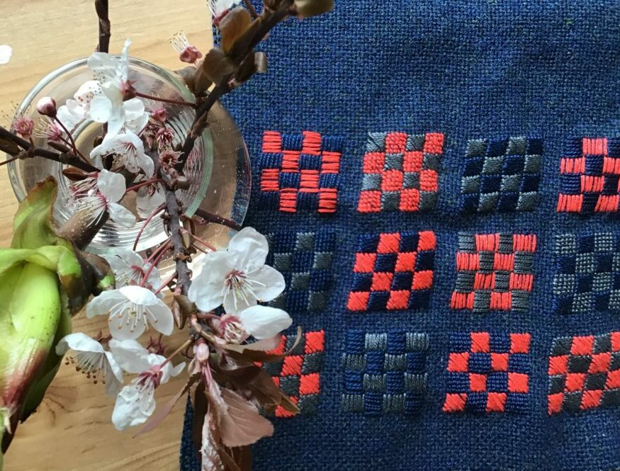 Embroidery on blue wool fabric which will be made into a bag