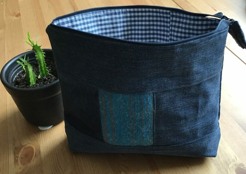 Wash bag with tambour embroidery sewn out of fabric from old jeans