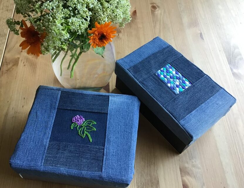 Two storage boxes decorated with old jeans and embroidery