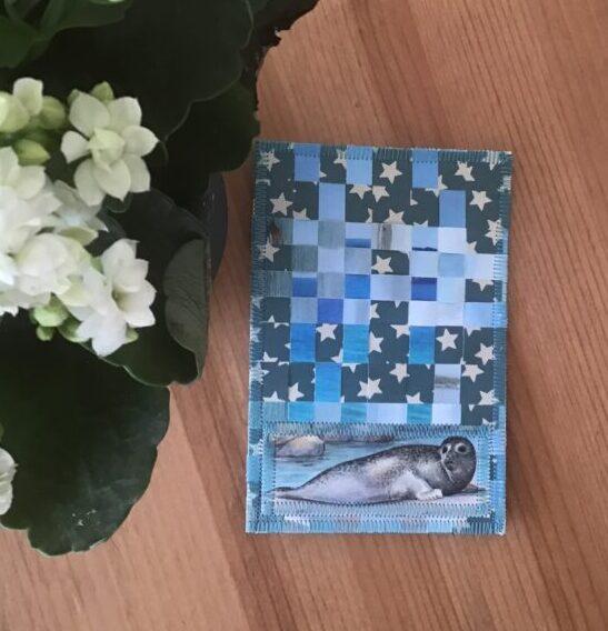 Fødselsdagskort flettet af genbrugspapir med en lille sæl